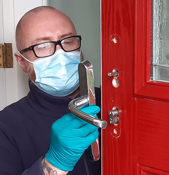 Fitter Lee Harrison refitting the door handle after upgrading the lock to a secure anti snap lock meeting Secured by Design standard